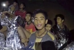 In this July 3, 2018, image taken from video provided by the Royal Thai Navy Facebook Page, Thai boys smile as Thai Navy SEAL medic help injured children inside a cave in Mae Sai, northern Thailand.  The Thai soccer teammates stranded more than a week in the partly flooded cave said they were healthy on a video released Wednesday, as heavy rains forecast for later this week could complicate plans to safely extract them. (Royal Thai Navy Facebook Page via AP)