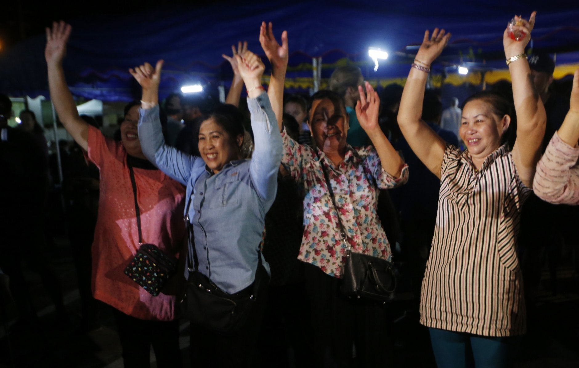 Peoples celebrate after evacuation in Chiang Rai as divers evacuated some of the 12 boys and their coach trapped at Tham Luang cave in the Mae Sai district of Chiang Rai province, northern Thailand, Tuesday, July 10, 2018. Thai Navy SEALs say all 12 boys and their coach were rescued from the cave, ending an ordeal that lasted more than 2 weeks. (AP Photo/Sakchai Lalit)