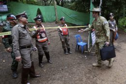 Australian Federal Police and Defense Force personnel arrive near a cave where 12 boys and their soccer coach have been trapped since June 23, in Mae Sai, Chiang Rai province, in northern Thailand Sunday, July 8, 2018. Thai authorities are racing to pump out water from the flooded cave before more rains are forecast to hit the northern region. (AP Photo/Sakchai Lalit)