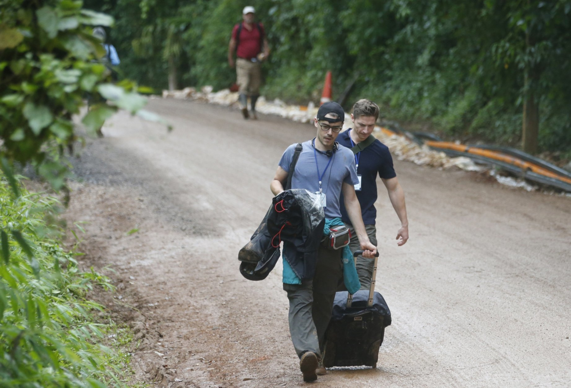 Media staff leave the area around the entrance of the cave where 12 boys and their soccer coach have been trapped for two weeks, in Mae Sai, Chiang Rai province, in northern Thailand Sunday, July 8, 2018. Thai authorities asked media to leave the area, fueling speculation on Sunday morning that a rescue mission could be imminent. (AP Photo/Sakchai Lalit)