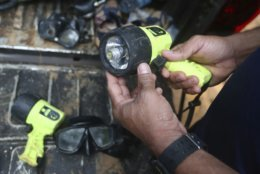 In this Tuesday, July 3, 2018, file photo, a rescuer prepares a light for diving to reach the 12 boys and their soccer coach found alive in a flooded cave in Mae Sai, Chiang Rai province, northern Thailand. (AP Photo/Sakchai Lalit)