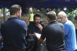 In this Thursday, July 2018, file photo, Australian Federal Police and Defense Force personnel talk about extraction plans to get 12 boys and their soccer coach out of a flooded cave in Mae Sai, Chiang Rai province, in northern Thailand. (AP Photo/Sakchai Lalit, File)