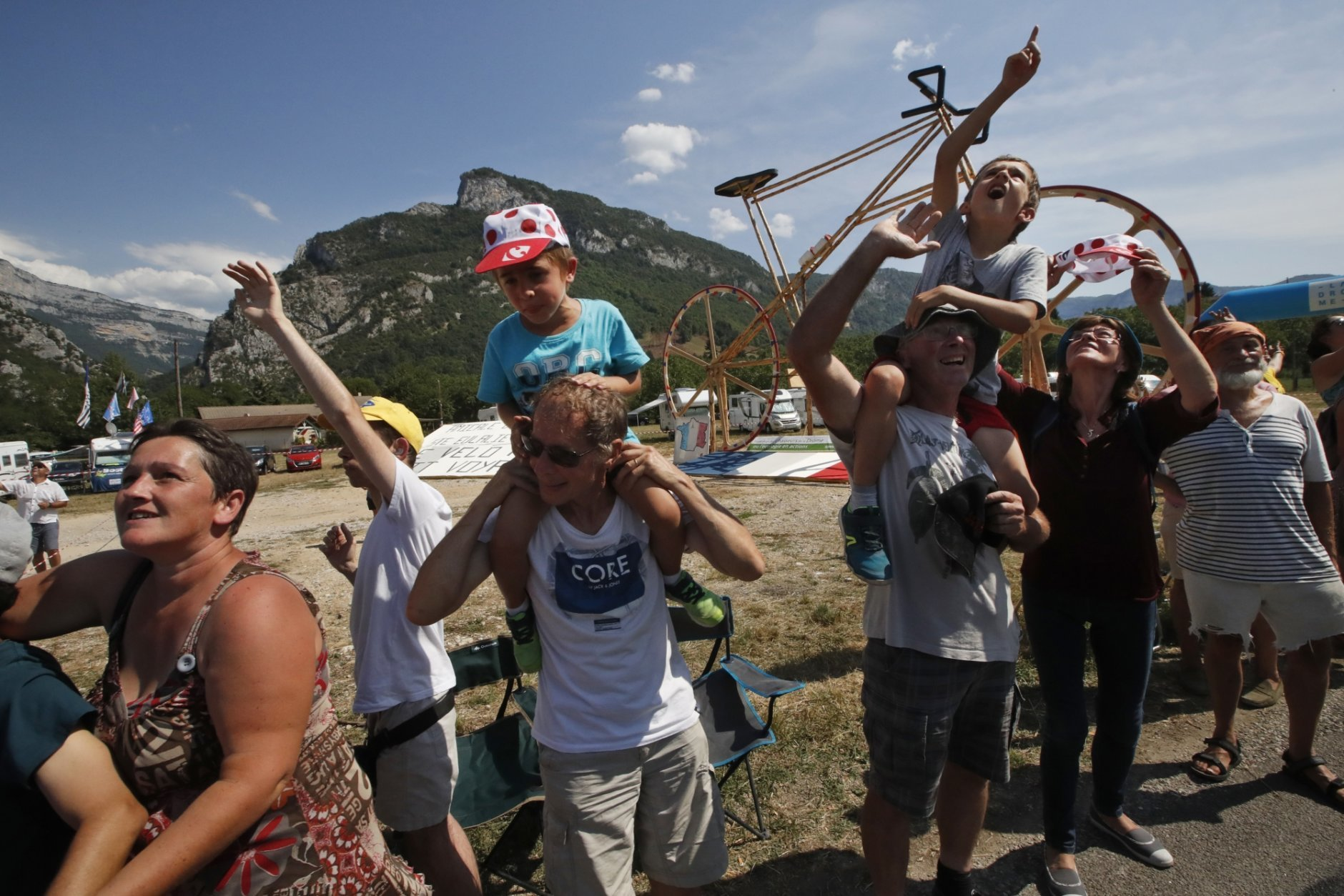 Fans lining the road look up at helicopters passing overhead during the thirteenth stage of the Tour de France cycling race over 169.5 kilometers (105.3 miles) with start in Bourg d'Oisans and finish in Valence, France, Friday July 20, 2018. Tour organizers estimate that 10 to 12 million spectators line the route each year. (AP Photo/Christophe Ena )