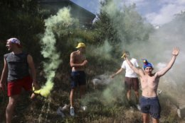 Fans set off flares as the group of leaders passes during the twelfth stage of the Tour de France cycling race over 175.5 kilometers (109 miles) with start in Bourg-Saint-Maurice Les Arcs and Alpe d'Huez, France, Thursday July 19, 2018. Superhero costumes, bunny outfits, shirtless, Tour de France spectators come in every color. (AP Photo/Peter Dejong)