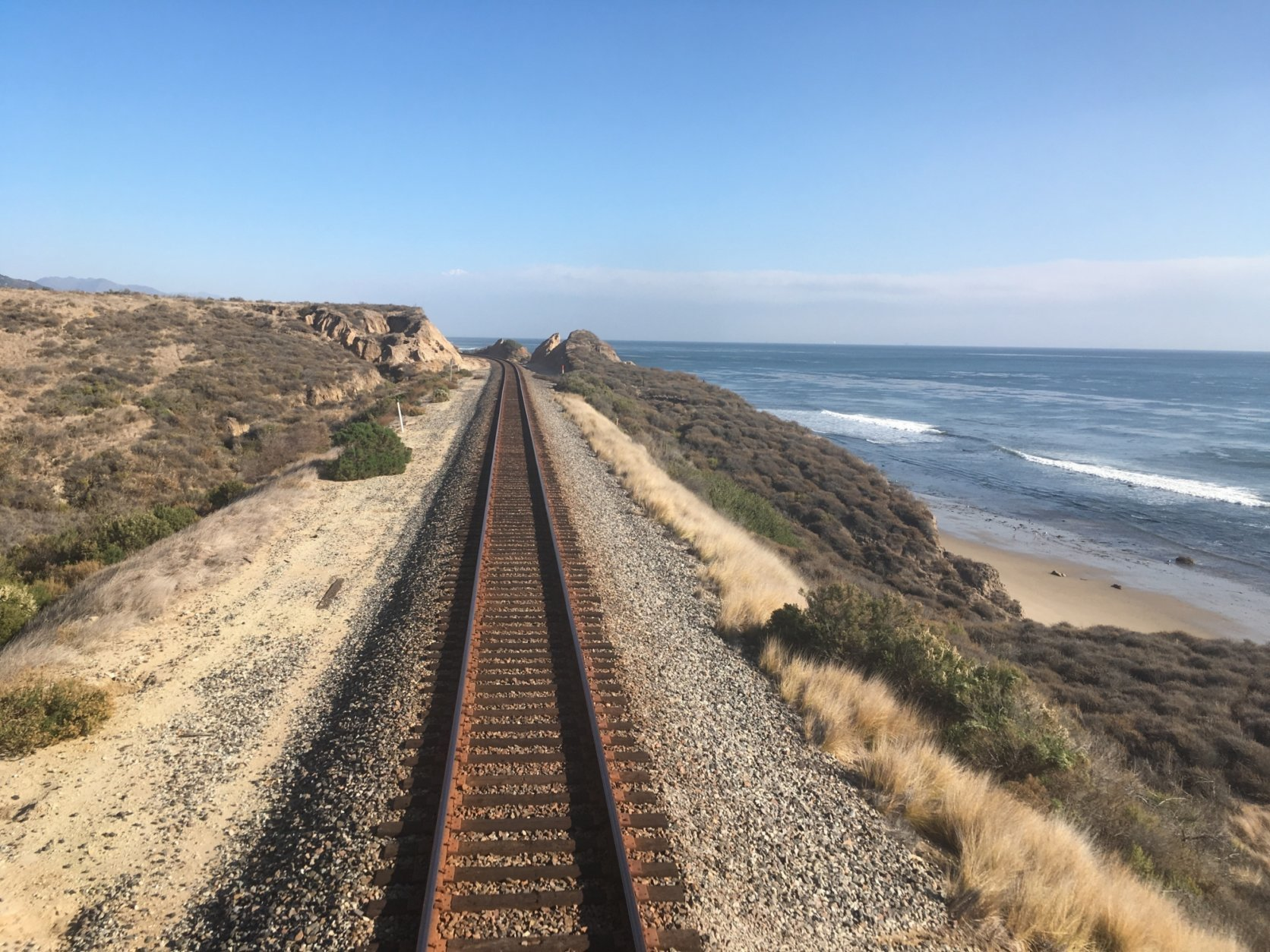This Dec. 16, 2017 photo shows the northern California coastline from the window of Amtrak's Coast Starlight as the train journeys to Seattle from Los Angeles. Skip the hassles of traffic and airport security and hop on a coastal trek offering an old-fashioned, unplugged escape with scenic views of the Pacific Northwest. Seattle is the destination on Amtrak's 35-hour Coast Starlight sleeper train, but the relaxing journey is the main attraction. (AP Photo/Nicole Evatt)