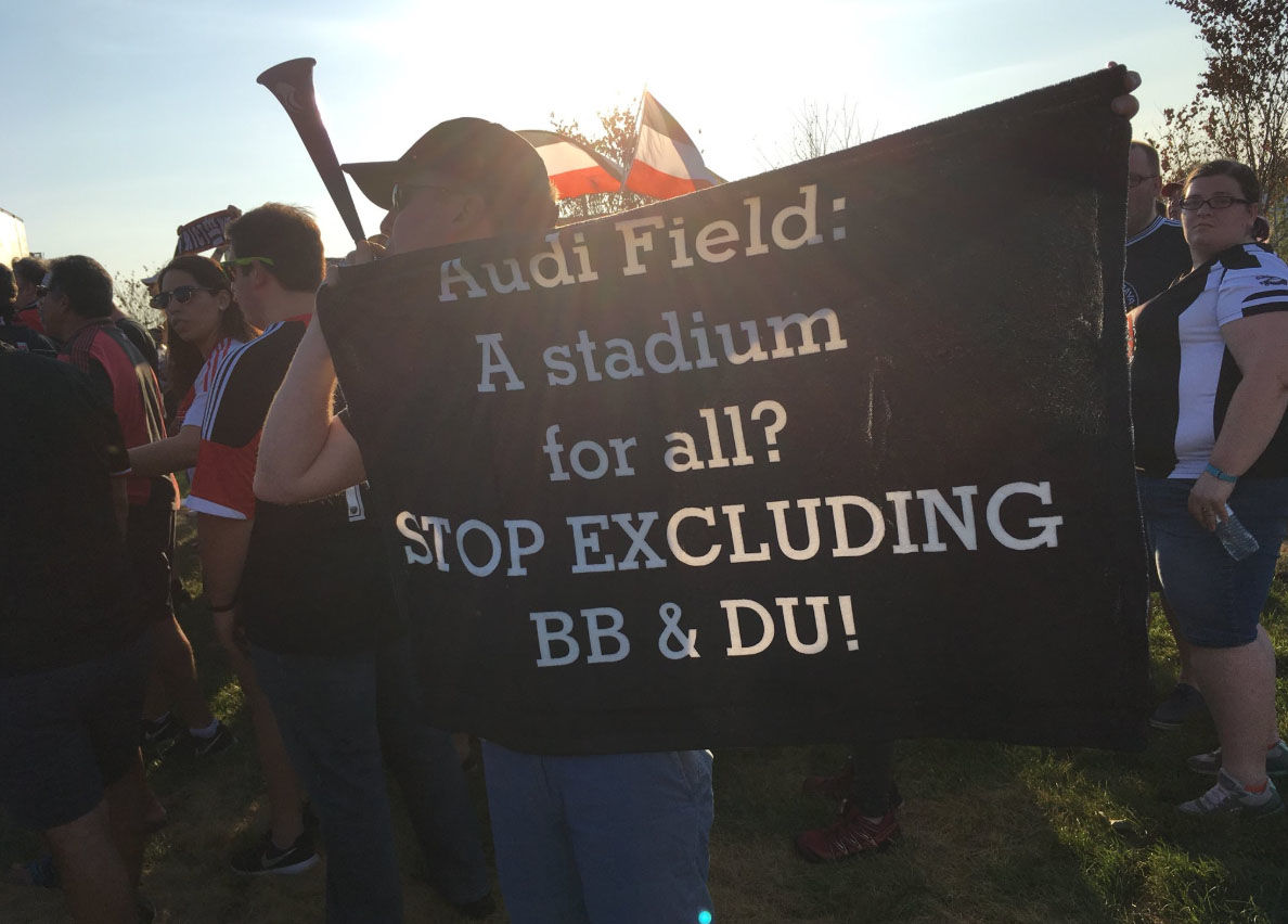 A protesters holds a sign outside Audi Field during D.C. United's first game in the new stadium. (WTOP/Liz Anderson)