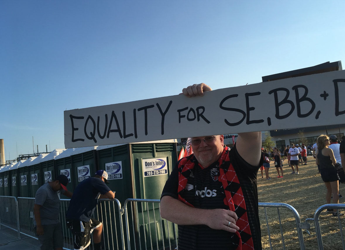 A protester holds a sign during D.C. United's first game at Audi Field on Saturday, July 18, 2018. (WTOP/Liz Anderson)