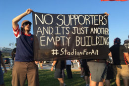 Protesters hold signs during D.C. United's first game at Audi Field on Saturday, July 14, 2018. (WTOP/Liz Anderson)