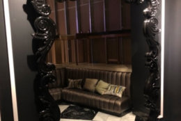 An ornate oversized framed mirror with black finish. (Courtesy Rasmus Auctions)