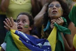 Worried Brazil soccer fans watch a live telecast of the Brazil vs. Belgium World Cup quarter finals soccer match, in Rio de Janeiro, Brazil, Friday, July 6, 2018. (AP Photo/Silvia Izquierdo)