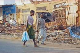 Kigali residents walk past debris in the city center, Wednesday, August 3, 1994. The U. S. Embassy reopened for the first time since a genocidal rampage caused most foreigners to leave nearly four months ago. The death of Rwanda's president in a mysterious plane crash touched off ethnic slaughter and reignited a civil war that together claimed 350,000 to 500,000 lives. Most of the dead were minority Tutsis slain by Hutu soldiers and militiamen. The victorious Tutsi-dominated rebels installed a new government July 18. (AP Photo/Dominic Cunningham-Reid)