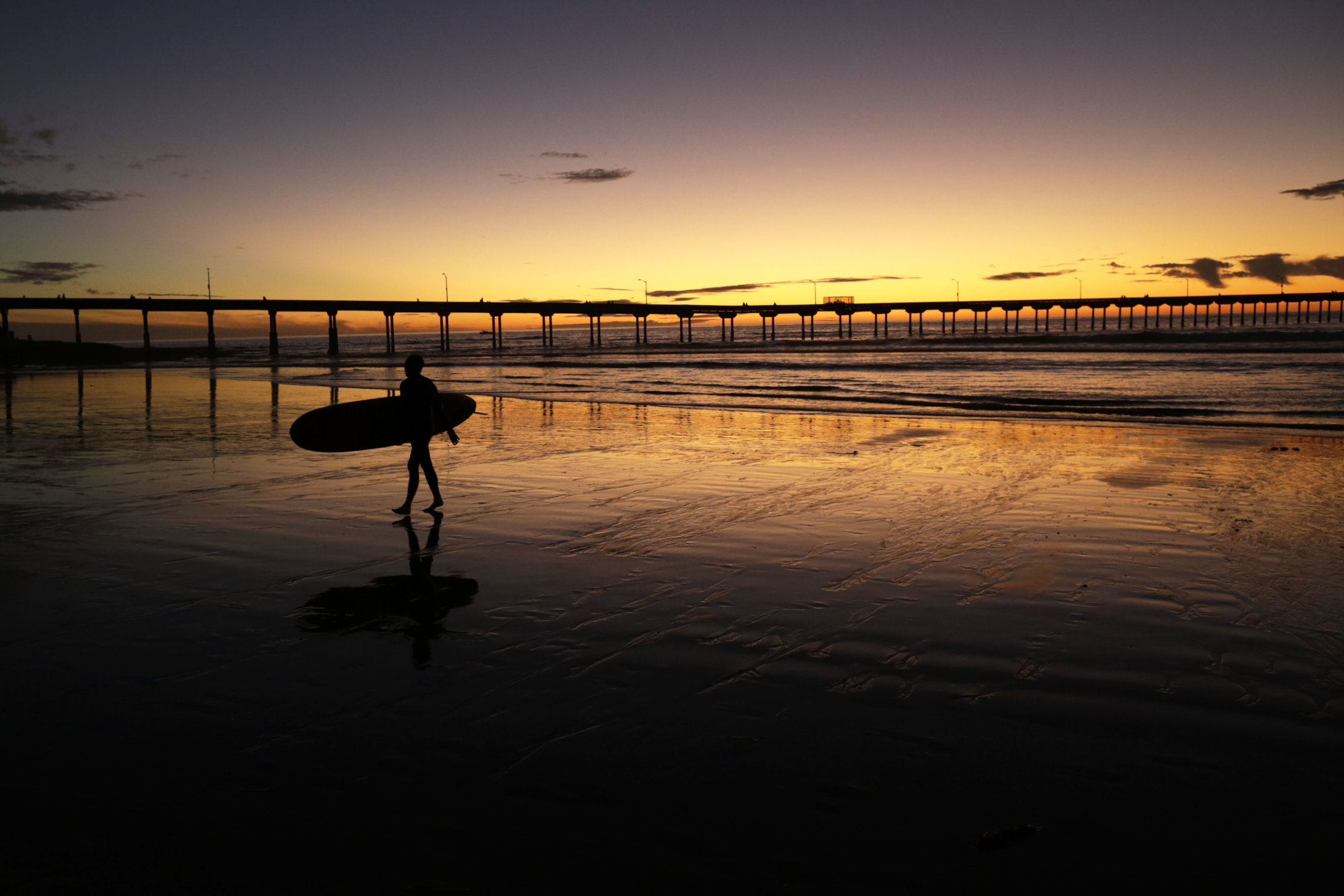 A surfer walks out of the surf as the sun sets behind Ocean Beach pier Tuesday, Nov. 7, 2017, in San Diego. (AP Photo/Gregory Bull)