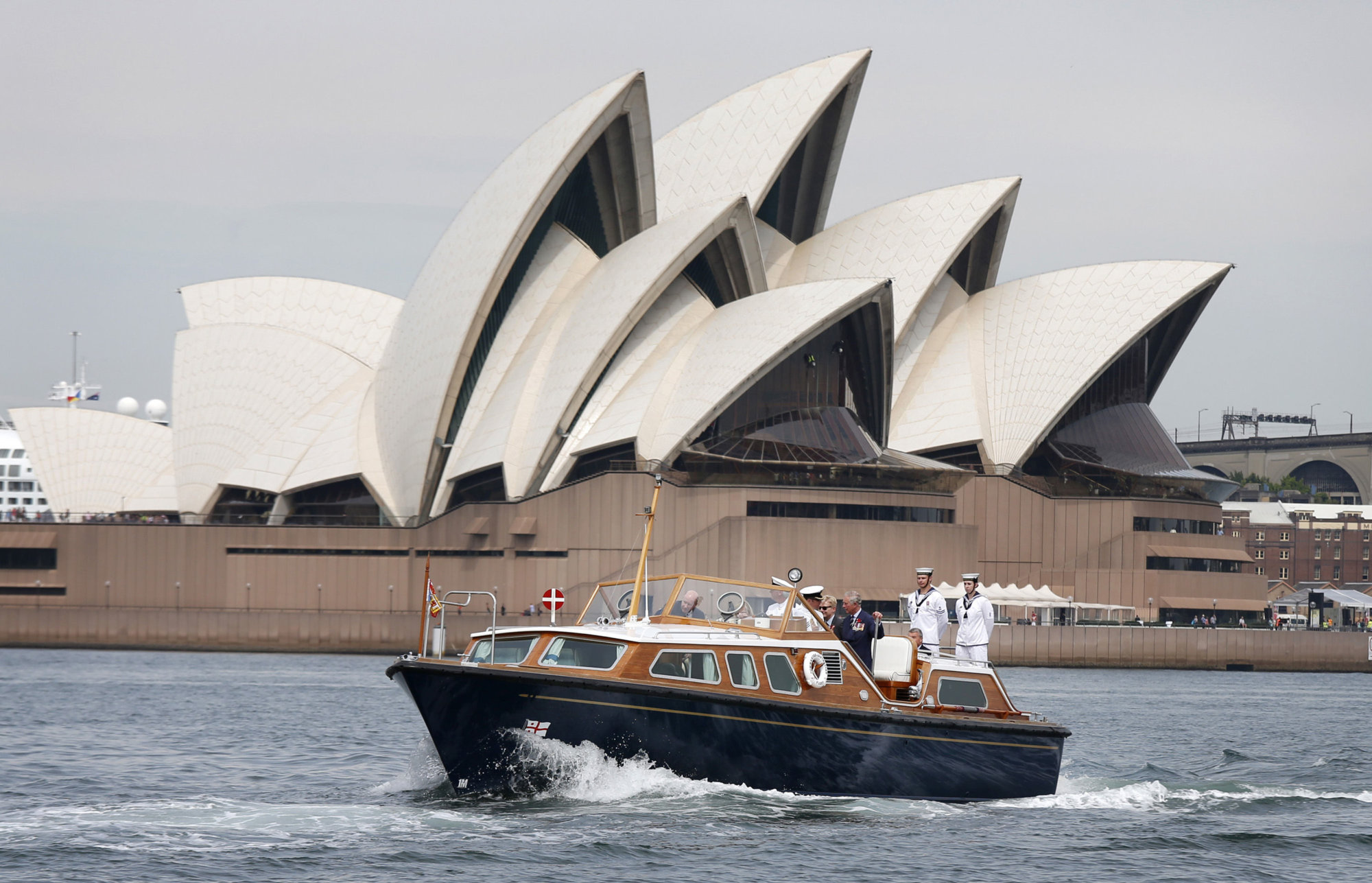 Britain's Prince Charles, at center in blue suit, travels on the Admiral's Barge past the Sydney Opera House as he crosses Sydney Harbour in Sydney, Australia Friday, Nov. 9, 2012. (AP Photo/Tim Wimborne, Pool)