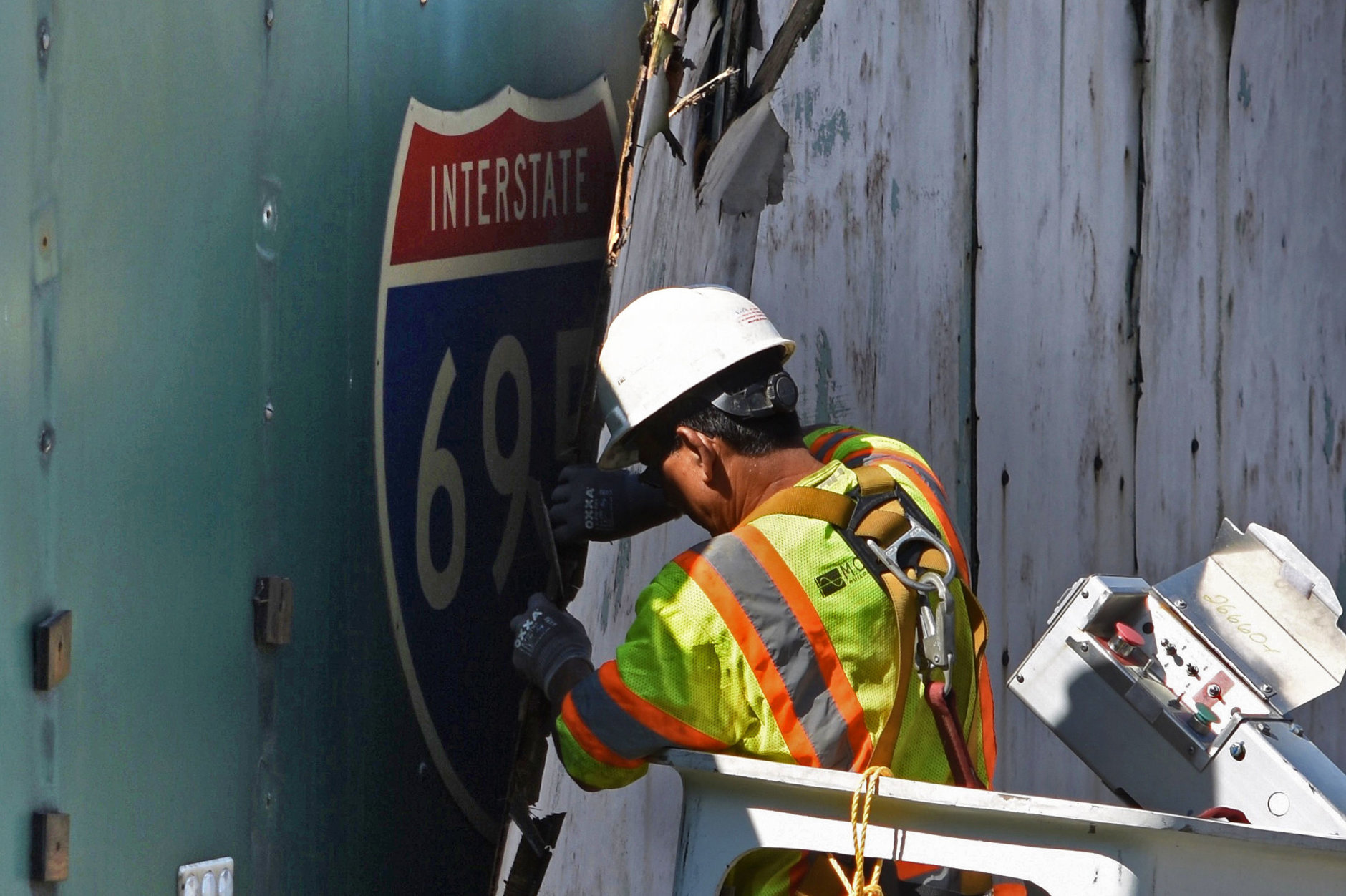 A DDOT contractor peels back a sheet of plywood, revealing an overhead sign pointing toward the never-built South Leg of the I-695 Inner Loop Freeway.  (WTOP/Dave Dildine)
