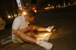Joung Yun of Flushing, Queens, reads a newpaper by flashlight as he sits on the sidewalk at New York's Fifth Ave. early Friday morning Aug. 15, 2003. A power outage hit most of northeastern United States Thursday afternoon, leaving the city in the dark. (AP Photo/Joe Kohen)