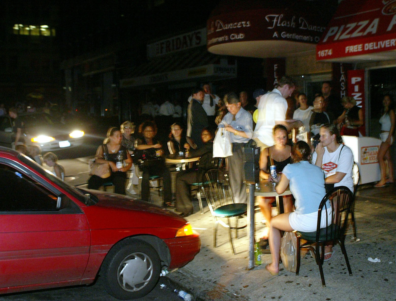 Patrons eat and drink outside Leon's Pizza in midtown Manhattan in New York, under the lights of a parked car, during a blackout, Thursday, Aug. 14, 2003. Night descended on New York shortly after 4  p.m., Thursday, when power went out throughout the five boroughs and most of its suburbs.  (AP Photo/Joe Kohen)