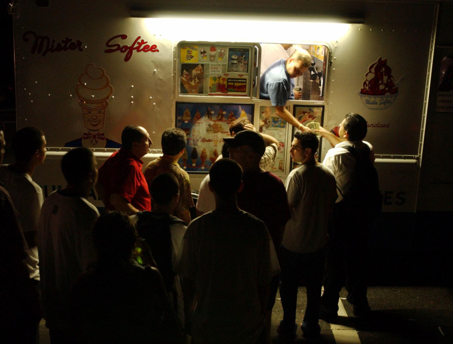 Patrons crowd a Mister Softee ice cream truck to buy ice cream as darkness envelops Weehaken, N.J. during a massive power outage Thursday Aug. 14, 2003. A massive power blackout hit U.S. and Canadian cities Thursday. (AP Photo/Jacqueline Larma)