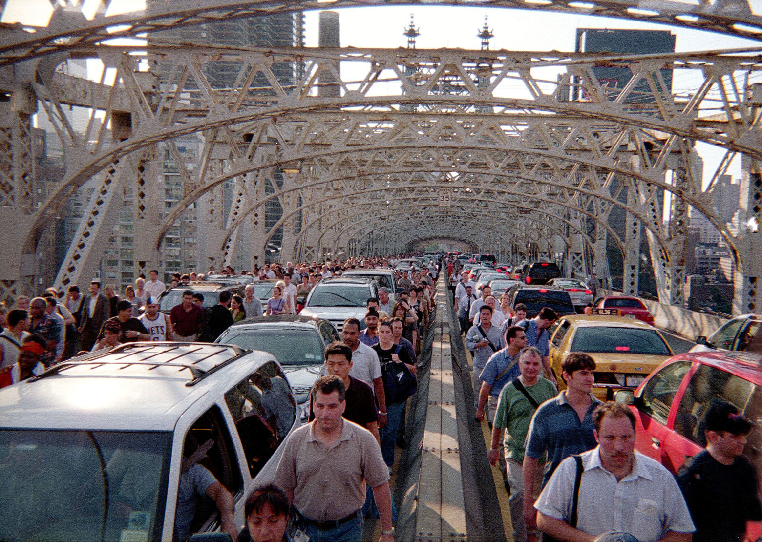 Commuters walk over the Queensborough Bridge with traffic stopped in gridlock in New York, Thursday, August 14, 2003 during a massive blackout which knocked out power in most of the Northeastern United States.  (AP Photo/Sean M. Thompson)