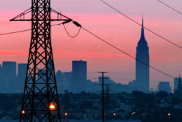 A darkened New York City is visible just before dawn through power lines from Jersey City, N.J., shown in foreground, with some lights visible, Friday, Aug. 15, 2003. The Empire State Building is in background.  (AP Photo/George Widman)