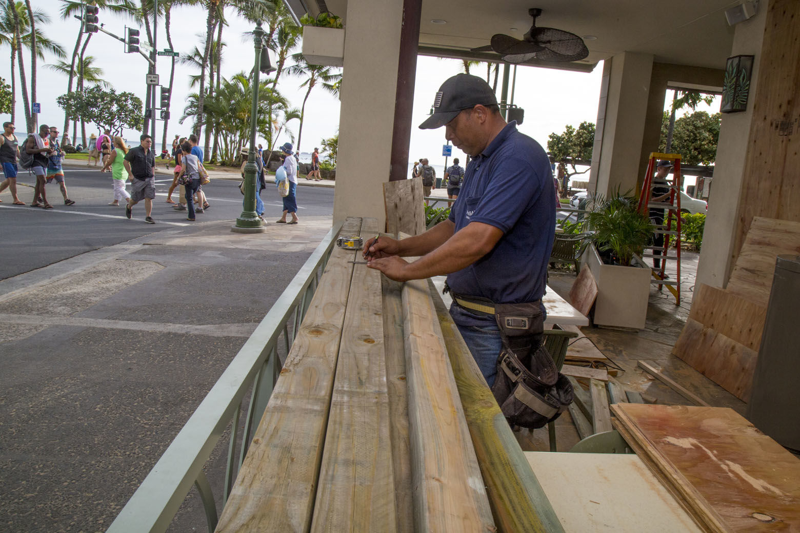 HONOLULU, HI - AUGUST 22:    Yamasaki Construction worker, foreman Nathan Koikoinui,  measures plywood to board up McDonalds multiple plate glass windows in preparation for Hurricane Lane on Kalaukaua Ave on Wednesday, August 22, 2018 in Honolulu, Hawaii. Hurricane Lane is a high-end Category 4 hurricane and remains a threat to the entire island chain. (Photo by Kat Wade/Getty Images)