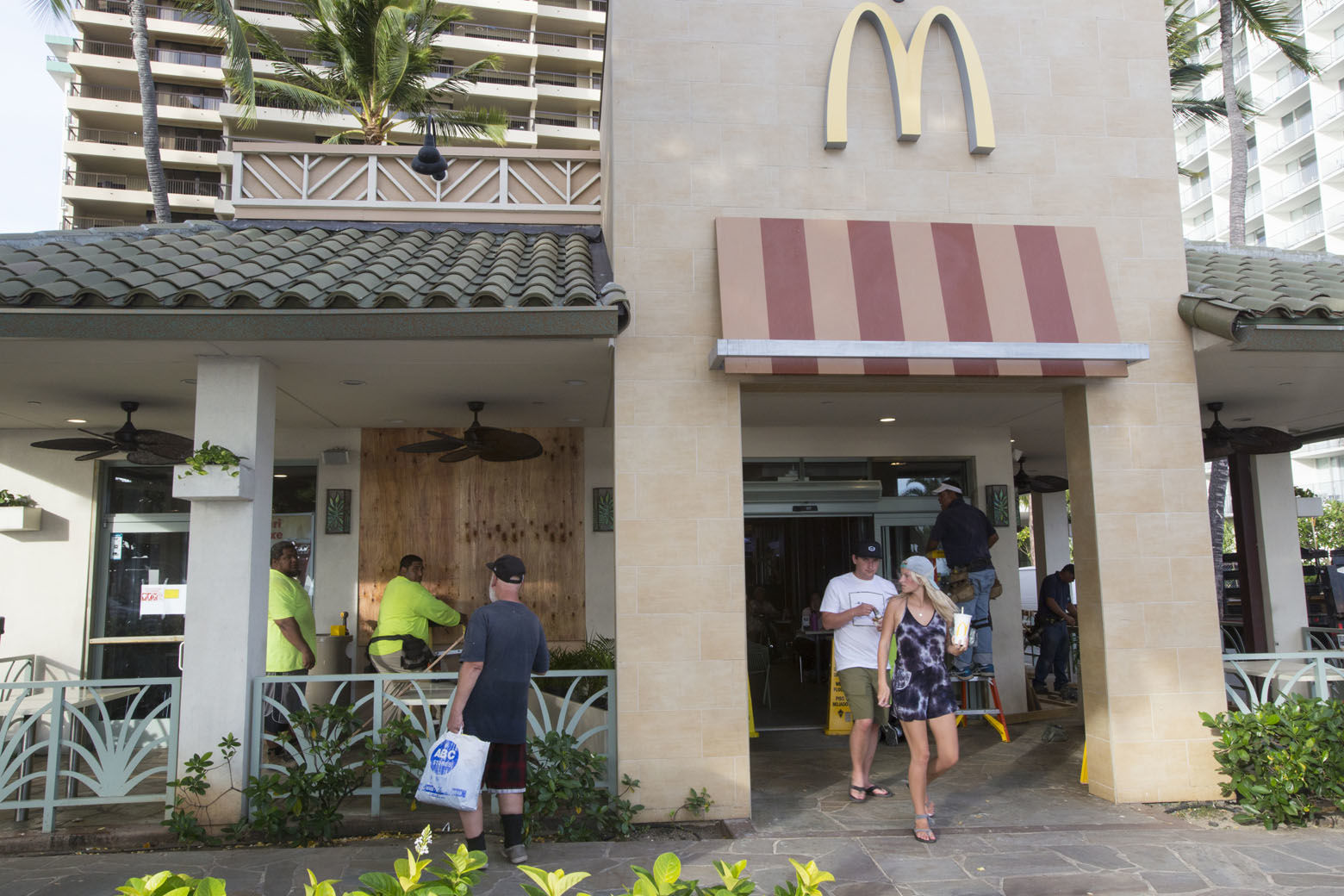 HONOLULU, HI - AUGUST 22:    Yamasaki Construction workers, Talbot Khakai, left, David Halafihi and Manly Williams board up McDonalds front plate glass windows in preparation for Hurricane Lane  while tourists Jordan and Amberly watch them work on Kalaukaua Ave on Wednesday, August 22, 2018 in Honolulu, Hawaii. Hurricane Lane is a high-end Category 4 hurricane and remains a threat to the entire island chain. (Photo by Kat Wade/Getty Images)