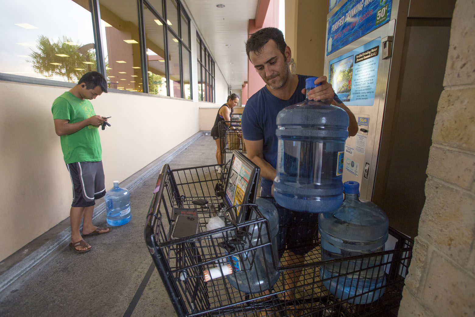 HONOLULU, HI - AUGUST 22: Wenkai He, left, waits his turn to fill up his 3 gallon water jug for just $1.50, while Alex Krivoulian fills three times as many water jugs at Safeway on Kapahulu in preparation for Hurricane Lane on Wednesday, August 22, 2018 in Honolulu, Hawaii. Hurricane Lane is a high-end Category 4 hurricane and remains a threat to the entire island chain. (Photo by Kat Wade/Getty Images)