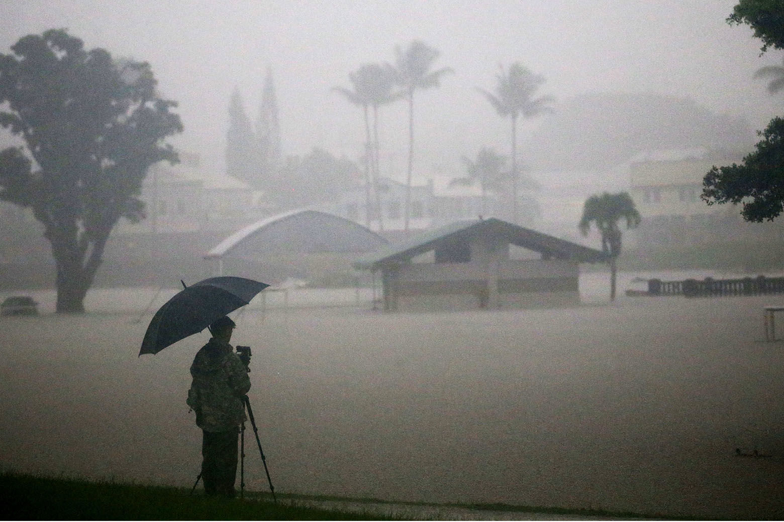 HILO, HI - AUGUST 23:  A man takes photos of floodwaters from Hurricane Lane rainfall on the Big Island on August 23, 2018 in Hilo, Hawaii. Hurricane Lane has brought more than a foot of rain to some parts of the Big Island which is under a flash flood warning.  (Photo by Mario Tama/Getty Images)