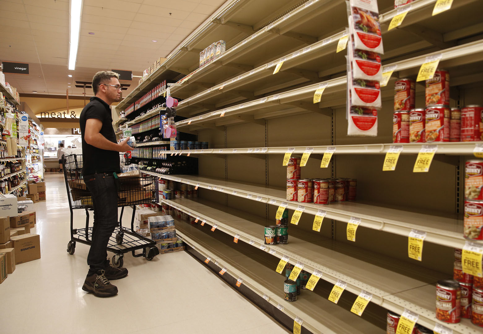 A worker looks at empty shelves for canned goods at a supermarket ahead of Hurricane Lane, Friday, Aug. 24, 2018, in Honolulu. (AP Photo/John Locher)