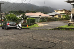 A utility line lays in the street in the Nuuanu neighborhood of Honolulu, Friday, Aug. 24, 2018, as Hurricane Lane approaches. Hurricane Lane barreled toward Hawaii on Friday, dumping torrential rains that caused flooding on the Big Island as people stocked up on supplies and piled sandbags to shield oceanfront businesses against the increasingly violent surf.  (AP Photo/Caleb Jones)