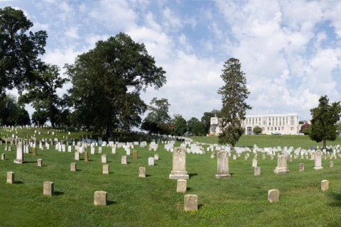 Who else is buried at US Naval Academy Cemetery in Annapolis?
