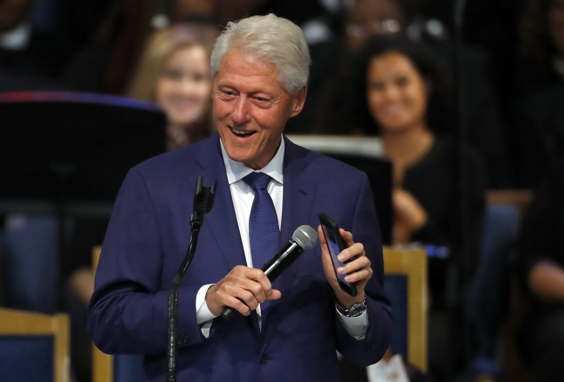 Former President Bill Clinton smiles as he plays a recording of Aretha Franklin on his phone during the funeral service for Franklin at Greater Grace Temple, Friday, Aug. 31, 2018, in Detroit. Franklin died Aug. 16, 2018 of pancreatic cancer at the age of 76. (AP Photo/Paul Sancya)