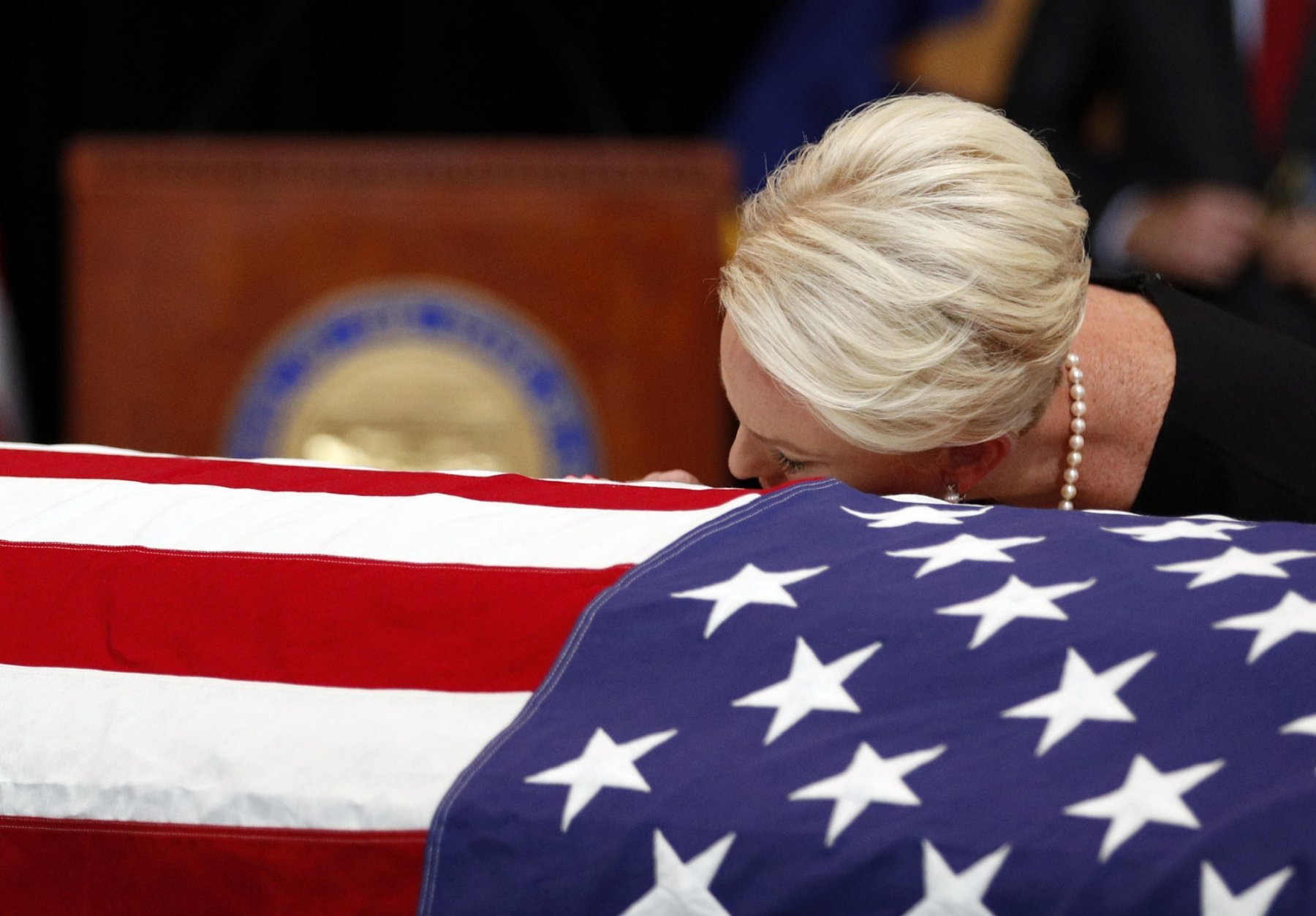 Cindy McCain, wife of, Sen. John McCain, R-Ariz. lays her head on the casket during a memorial service at the Arizona Capitol on Wednesday, Aug. 29, 2018, in Phoenix. (AP Photo/Jae C. Hong, Pool)