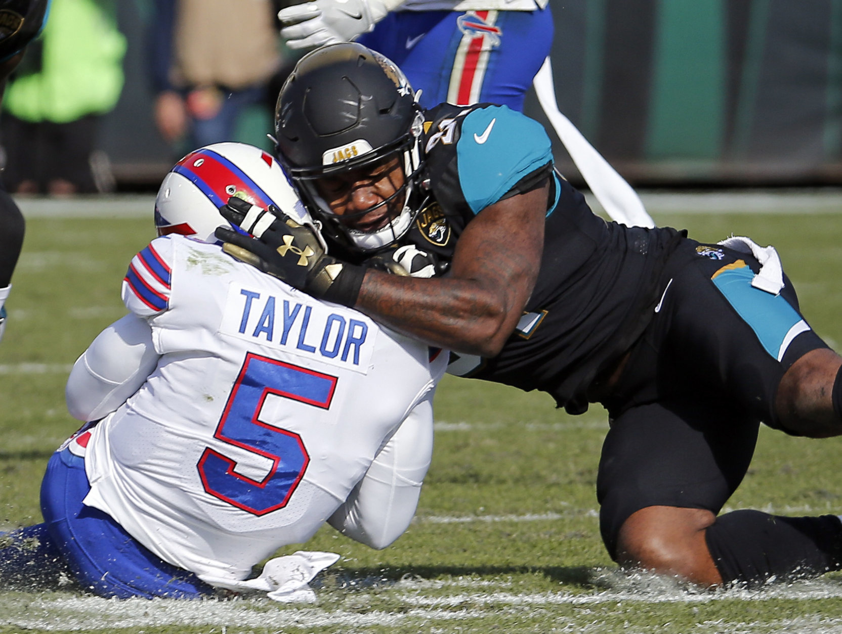FILE - In this Jan. 7, 2018, file photo, Jacksonville Jaguars defensive end Yannick Ngakoue, right, draws a penalty by hitting Buffalo Bills quarterback Tyrod Taylor (5) with helmet-to-helmet contact during the first half of an NFL wild-card playoff football game in Jacksonville, Fla. The NFL's new rule making it a penalty when a player leads with his helmet is generating plenty of grumbling about taking the football out of the sport, but more practically it's led to confusion about how it'll be enforced.  (AP Photo/Stephen B. Morton, File)