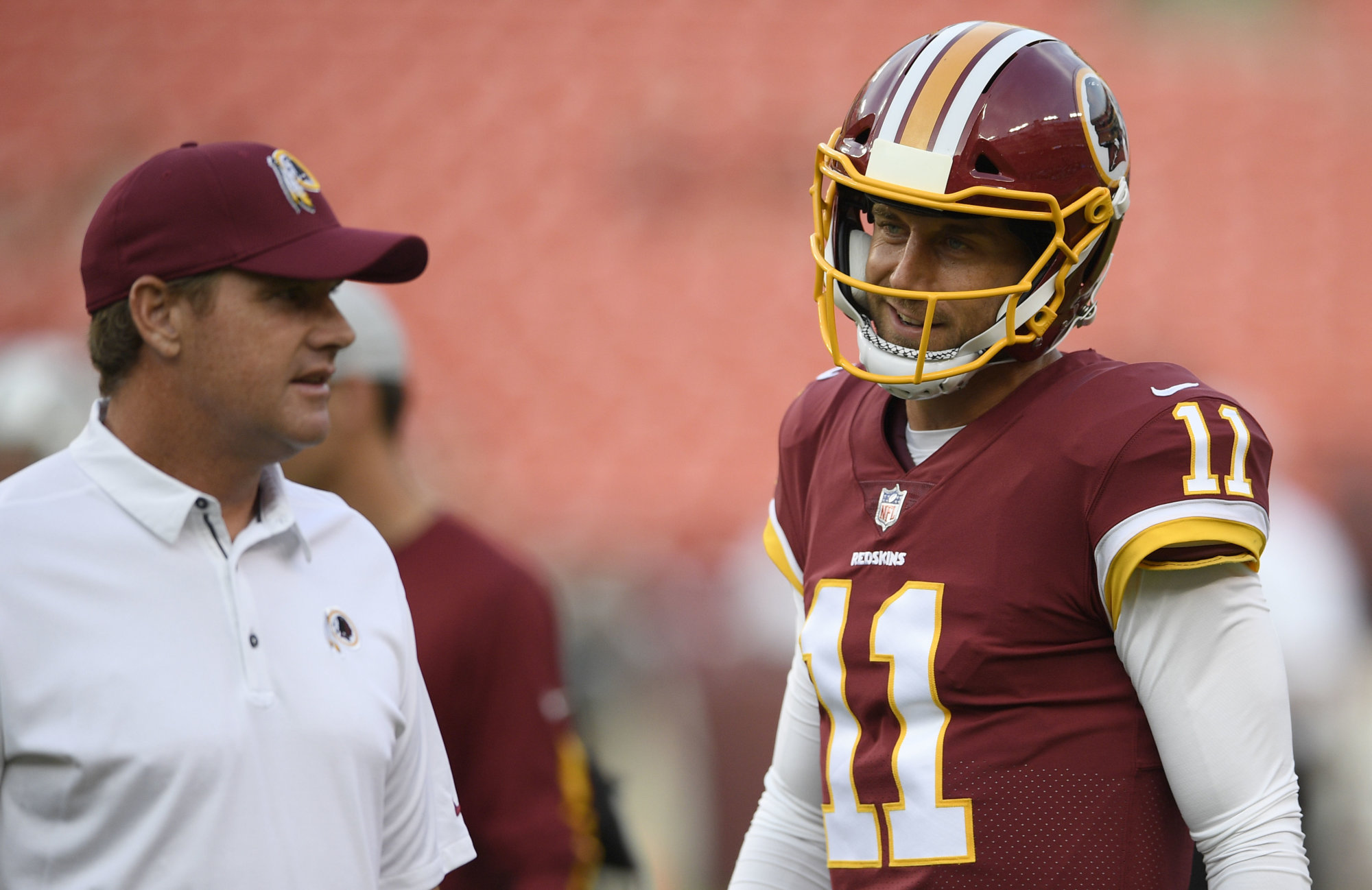 Washington Redskins quarterback Alex Smith (11) stands next to Washington Redskins head coach Jay Gruden, left, before a preseason NFL football game against the New York Jets, Thursday, Aug. 16, 2018, in Landover, Md. (AP Photo/Nick Wass)
