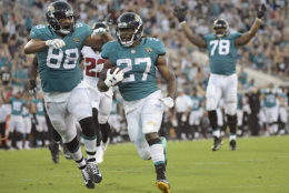 Jacksonville Jaguars running back Leonard Fournette (27) runs for a 21-yard touchdown against the Atlanta Falcons, next to tight end Austin Seferian-Jenkins (88), as offensive tackle Jermey Parnell (78) signals the score during the first half of an NFL preseason football game Saturday, Aug. 25, 2018, in Jacksonville, Fla. (AP Photo/Phelan M. Ebenhack)