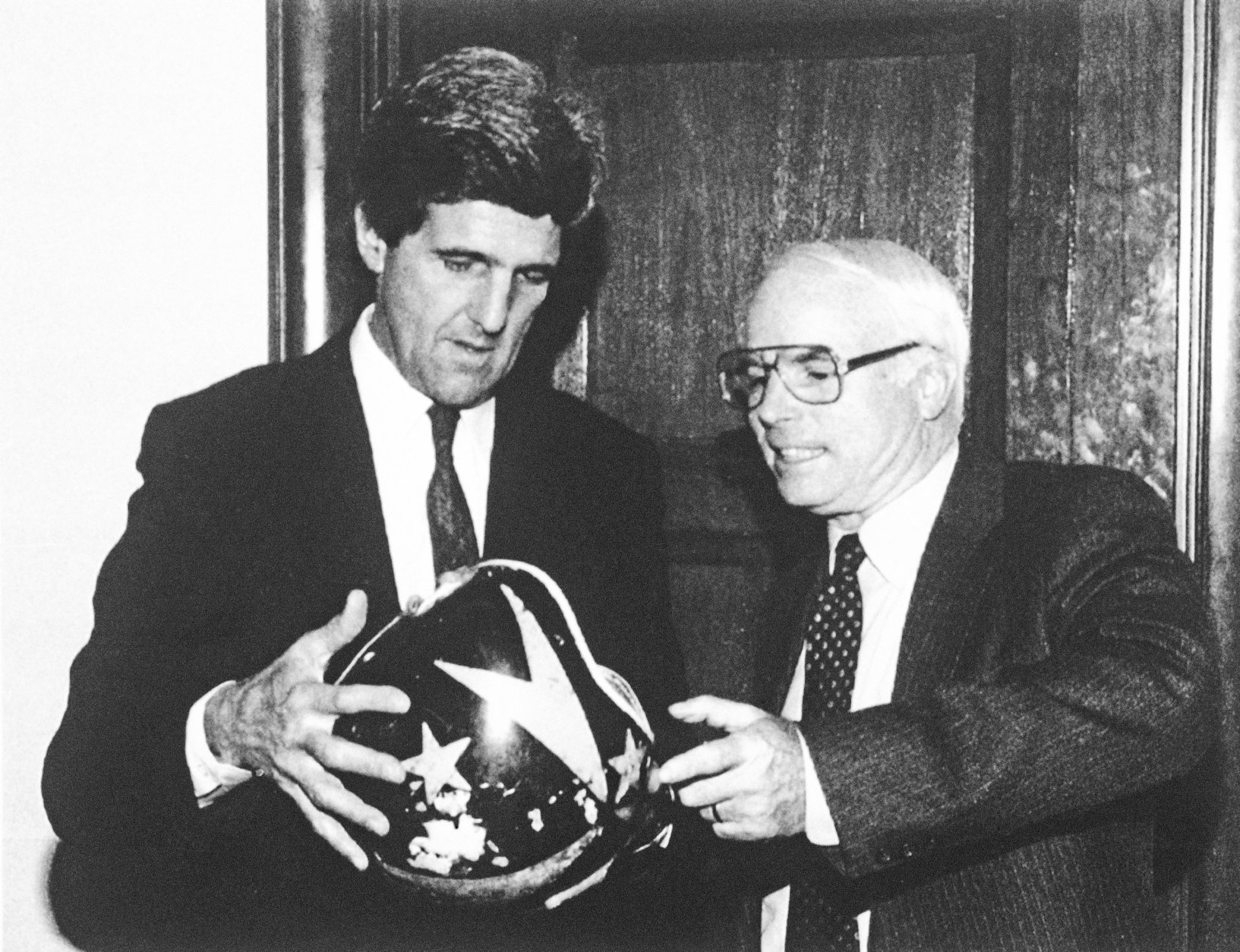 Sen. John Kerry (D-Mass.), chairman of the Senate Select Committee on POW-MIA Affairs, left, gives Sen. John McCain (R-Ariz.), a member of the committee, his pilot's helmet on Capitol Hill in Washington, Dec. 2, 1992. Kerry gave the helmet to McCain after retrieving it from the Vietnamese on a recent trip to Hanoi to investigate the POW/MIA issue. McCain was held prisoner in Vietnam during the war. (AP Photo/U.S. Senate)