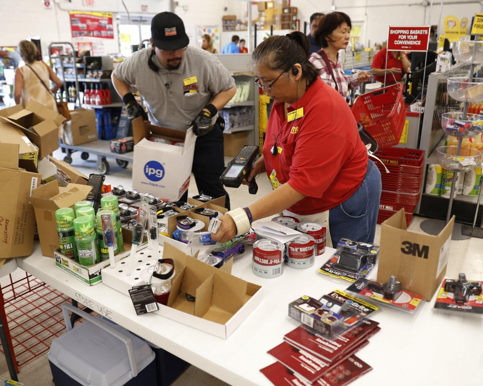 CORRECTS DAY TO AUG. 22- City Mill hardware store sales associates Frank Miller Gascon, left, Lisa Lavilla, fill a table up with duck tape, flashlights, and other hurricane supplies, Wednesday, Aug. 22, 2018, in Honolulu. Gascon said he's been filling the table up every ten minutes as supplies are being swept up by shoppers who are preparing for the approaching Hurricane Lane. Hurricane Lane has weakened as it approaches Hawaii but was still expected to pack a wallop, forecasters said Wednesday. (AP Photo/Marco Garcia)