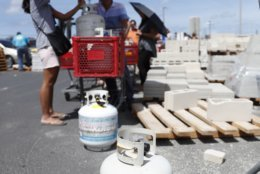CORRECTS DAY TO AUG. 22-People stand in a line waiting to fill up propane tanks at a local hardware store, Wednesday, Aug. 22, 2018, in Honolulu. Hurricane Lane has many Hawaii residents preparing for the worst. Hurricane Lane has weakened as it approaches Hawaii but was still expected to pack a wallop, forecasters said Wednesday. The National Weather Service said tropical-storm-force winds could begin as early as Wednesday afternoon on the Big Island. The hurricane was about 305 miles (490 kilometers) south of Kailua-Kona and moving northwest toward other islands. Meteorologist Chevy Chevalier in Honolulu says winds slowed overnight from 160 mph to 155 mph (259 to 250 kph), prompting a downgrade of the hurricane from a Category 5 to a Category 4. He says it may diminish to a Category 3 by Thursday afternoon but that would still be a major hurricane. Chevalier says that by early Friday, the hurricane is forecast to be a Category 2 with winds up to 110 mph (177 kph) and the center located west of Hawaii Island and south of Honolulu. (AP Photo/Marco Garcia)