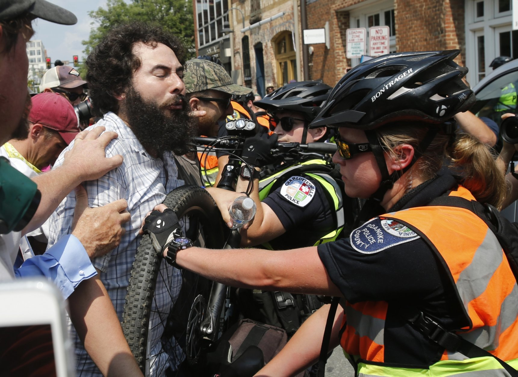 A demonstrator confronts police at the intersection where Heather Heyer was killed last year as they mark the anniversary of the Unite the Right rally in Charlottesville, Va., Sunday, Aug. 12, 2018. On that day, white supremacists and counterprotesters clashed in the city streets before a car driven into a crowd struck and killed Heyer. (AP Photo/Steve Helber)