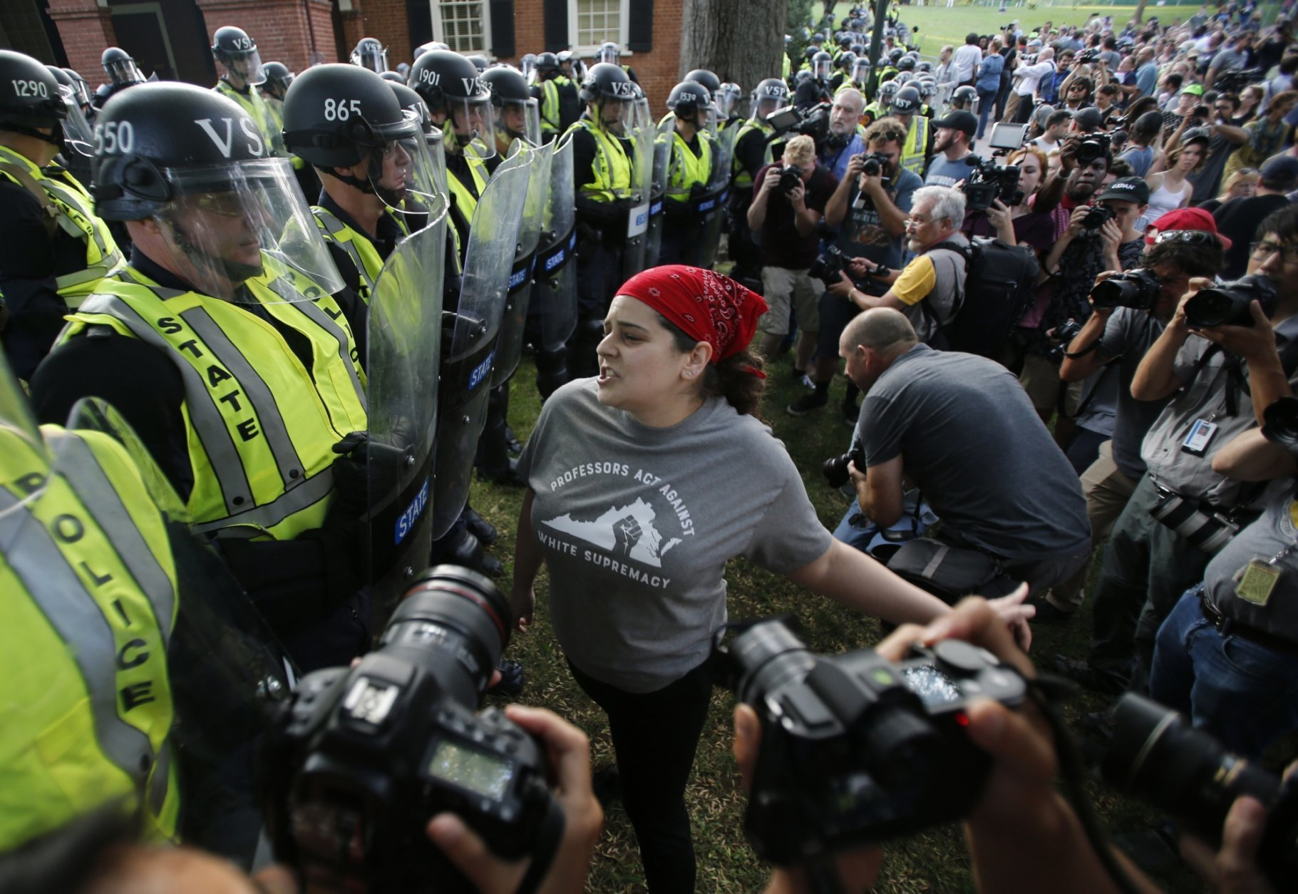A protester confronts riot gear-clad police on the campus of the University of Virginia during a rally to mark the anniversary of last year's Unite the Right rally in Charlottesville, Va., Saturday, Aug. 11, 2018. (AP Photo/Steve Helber)