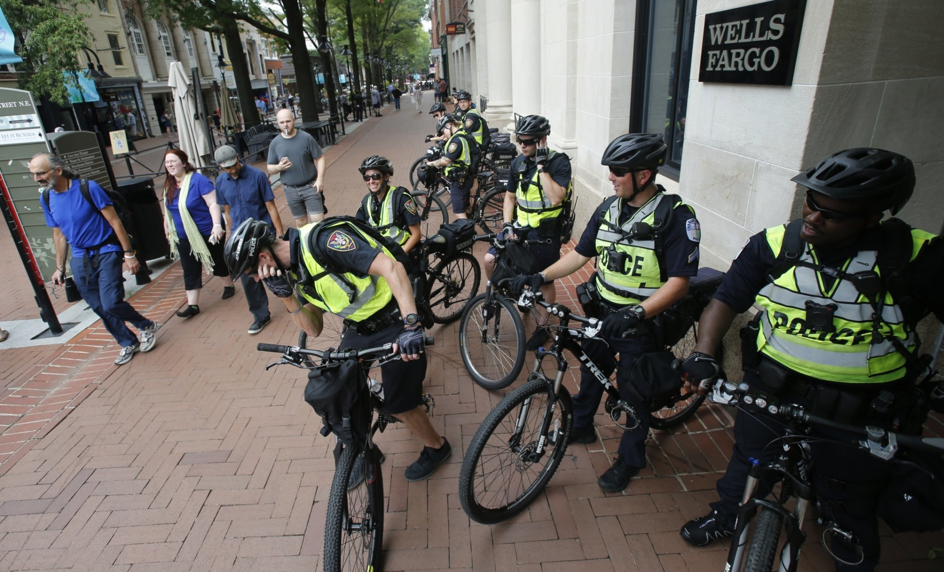 A Police bike patrol takes a break in the downtown area in anticipation of the anniversary of last year's Unite the Right rally in Charlottesville, Va., Saturday, Aug. 11, 2018. State and local authorities framed the weekend's heightened security as a necessary precaution. (AP Photo/Steve Helber)