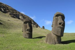 "FILE - In this August 2012 file photo, statues of heads known as ""Moais"" stand at Rano Raraku, the quarry on Easter Island, Chile. The 400 or so sculptures have bodies attached, but they are buried under the dirt and not visible. Chile's government is beginning to restrict tourism to the island, and have proposed to change Easter Island's name to ""Rapa Nui,"" as residents call the island. (AP Photo/Karen Schwartz, File)"