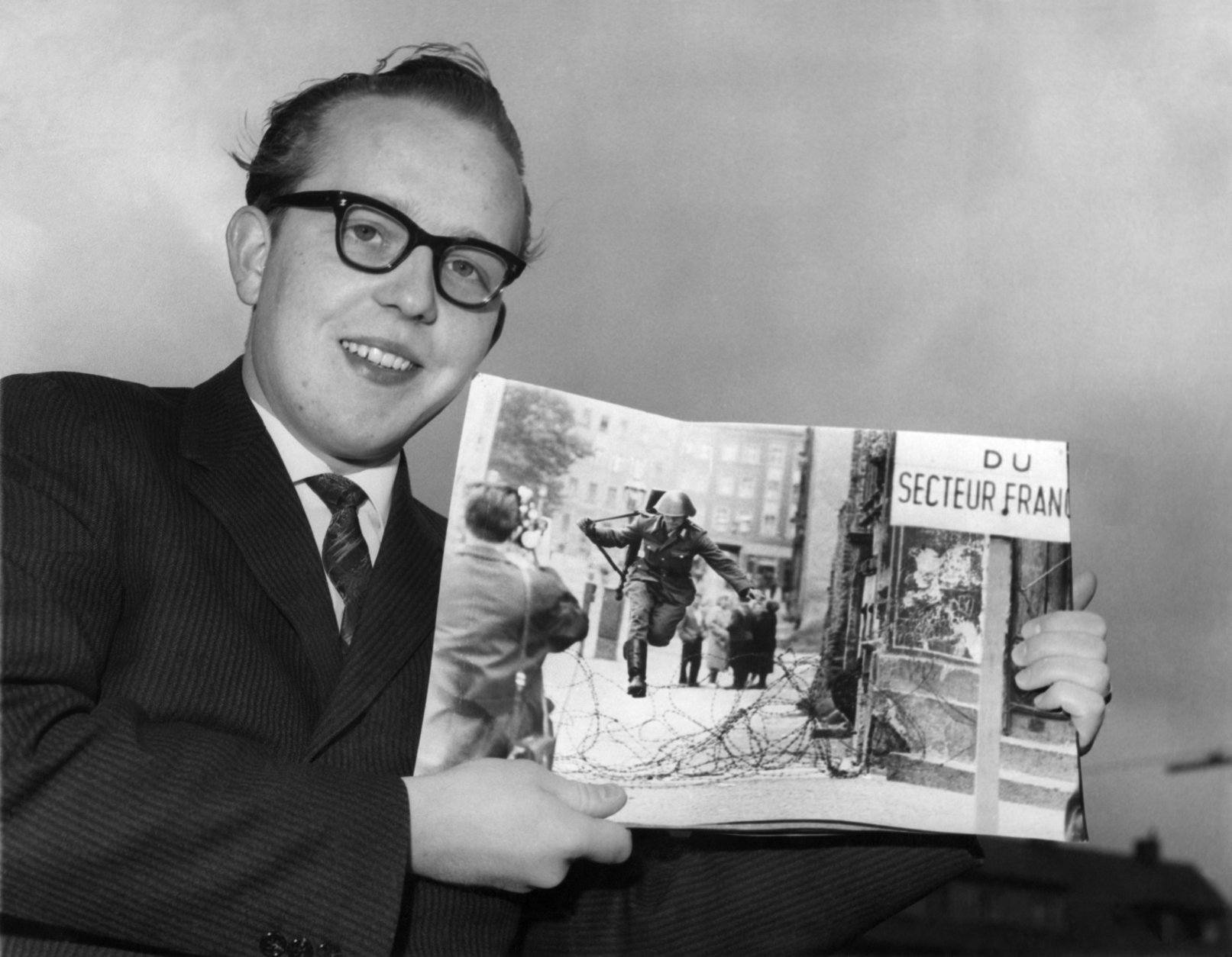 Peter Leibing, German press photographer in Hamburg, Germany, poses on April 15, 1962 with a copy of his dramatic shot of a communist East German army soldier clearing barbed wire at the Berlin sector border. Leibing made this picture when assigned to Berlin during dramatic August 1961 days, when the Reds set up the wall. The picture won him several prizes among them first prize of America's NPPA (National Press Photographers Association) as was announced on April 14, 1962. (AP Photo/Helmuth Lohmann)