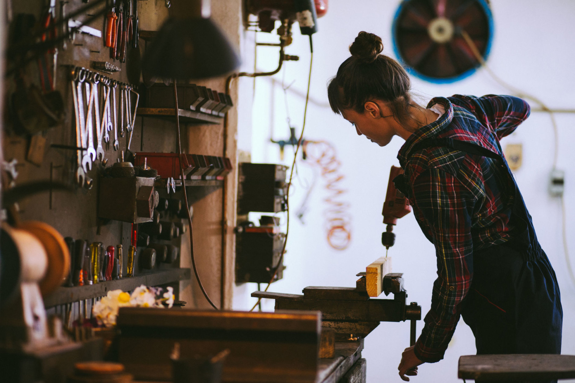 Attractive young brunette woman drilling part of the wood that's attached to clamp in her garage on working day.