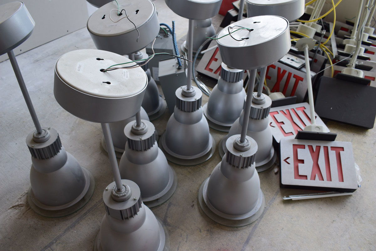 These light fixtures and emergency signs will soon have a new home in the WTOP space. (WTOP/Teta Alim)