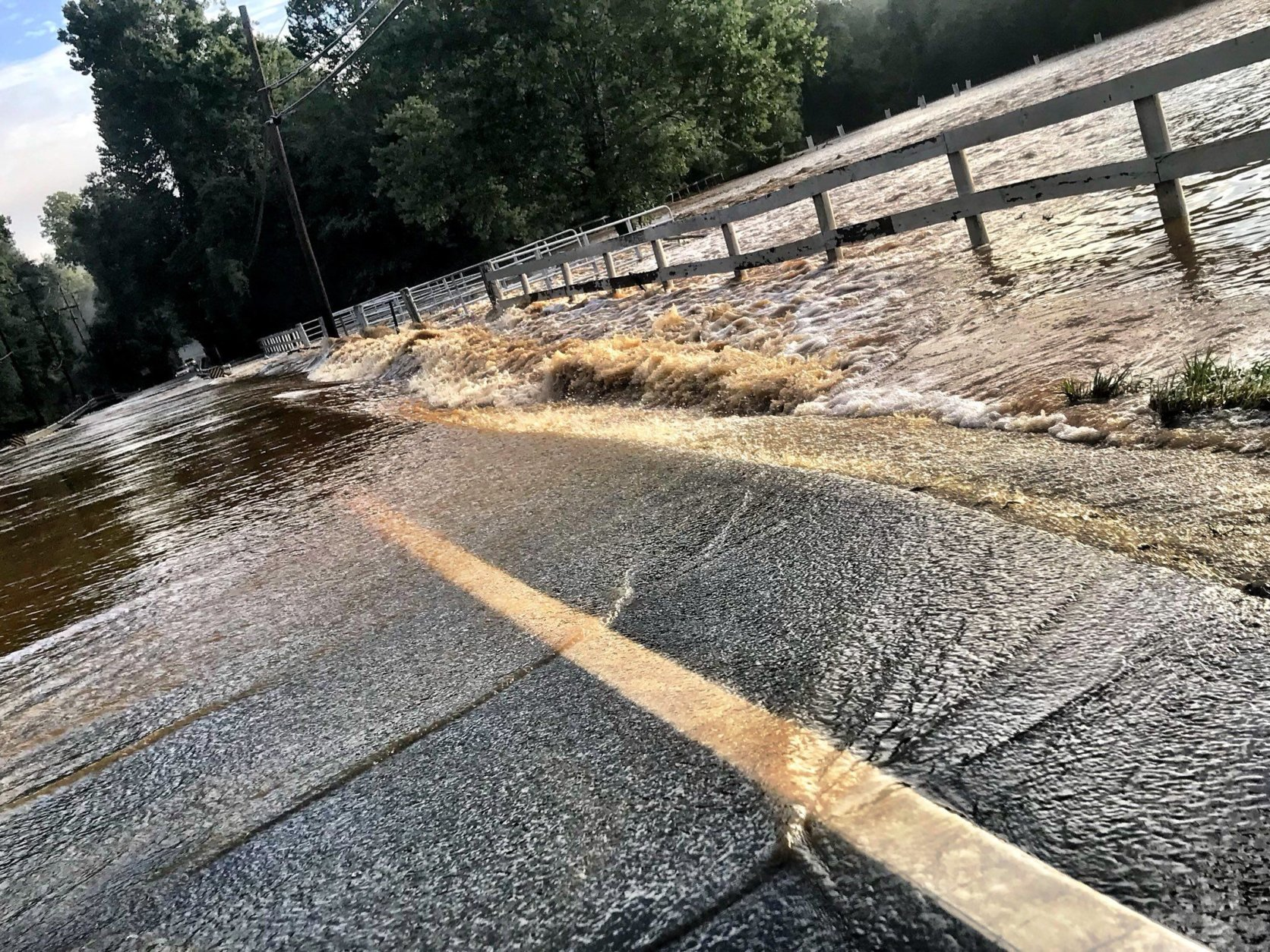 Flooding water from Difficult Creek pouring over Hunter Mill Road. (WTOP/Neal Augenstein)