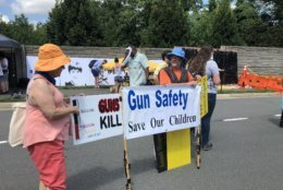 Protesters holding banners on Waples Mill Road, near the NRA's headquaters in Fairfax. (WTOP/Melissa Howell)