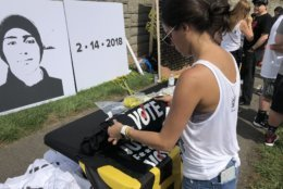 "A rally-goer looks at a shirt reading ""vote"""" across the street from the NRA. (WTOP/Melissa Howell)"