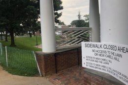 """A sign warning visitors that a sidewalk is closed is seen near the amphitheater for Saturday morning's """"The Hope that Summons Us"""" event at the University of Virginia. It comes one year after white supremacists marched through the Grounds with tiki torches, and a day before anniversary of Heather Heyer's death. (WTOP/Max Smith)"""