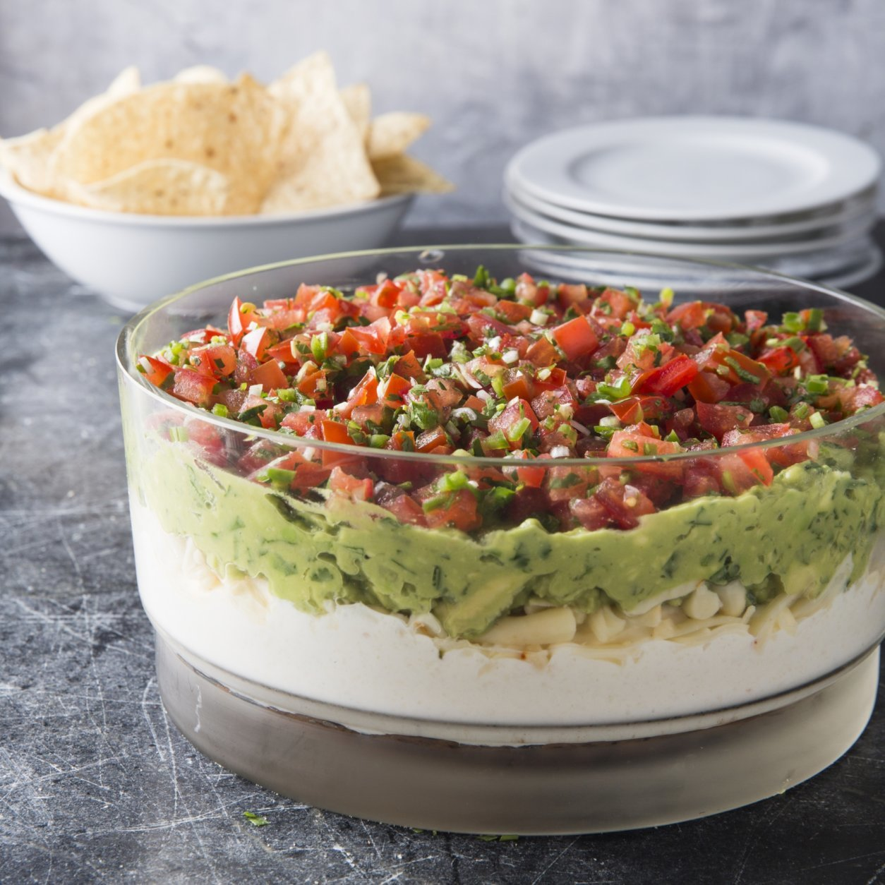 """This undated photo provided by America's Test Kitchen in July 2018 shows ultimate seven layer dip in Brookline, Mass. This recipe appears in the cookbook """"All-Time Best Appetizers."""" (Joe Keller/America's Test Kitchen via AP)"""